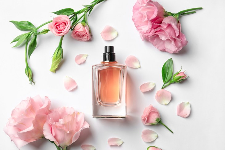 bottle of perfume surrounded by pink flowers
