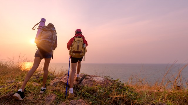 Two women hiking and looking at the sunset