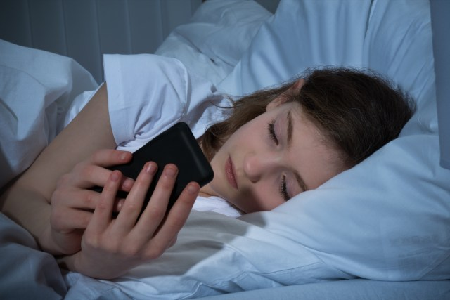 A woman using her phone while in bed