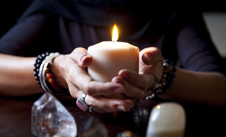 A women holding a candle with crystals and rocks in front