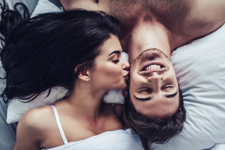 Happy couple lying in bed, woman kissing man on the cheek