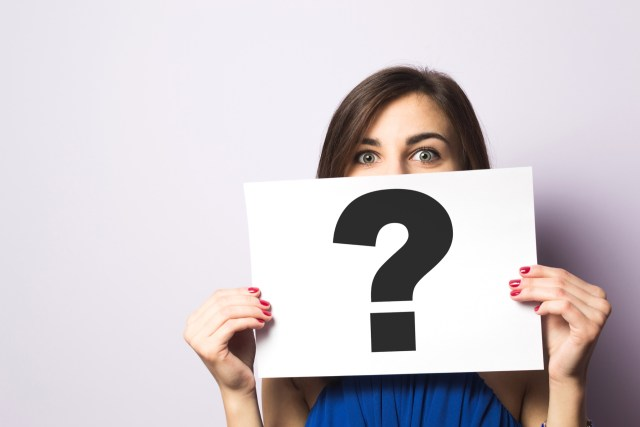 Young woman holding a question mark card