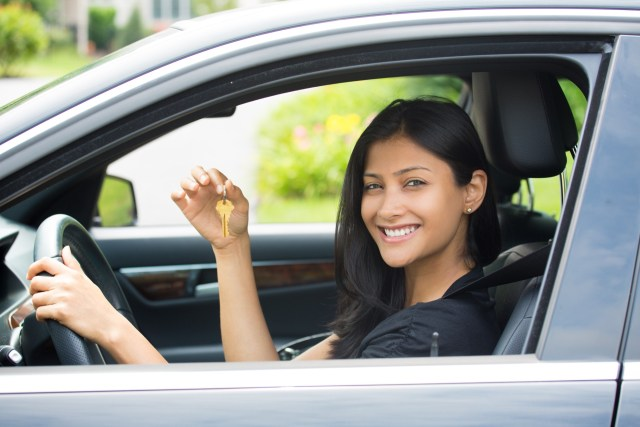 Girl smiling and holding keys to her brand new car
