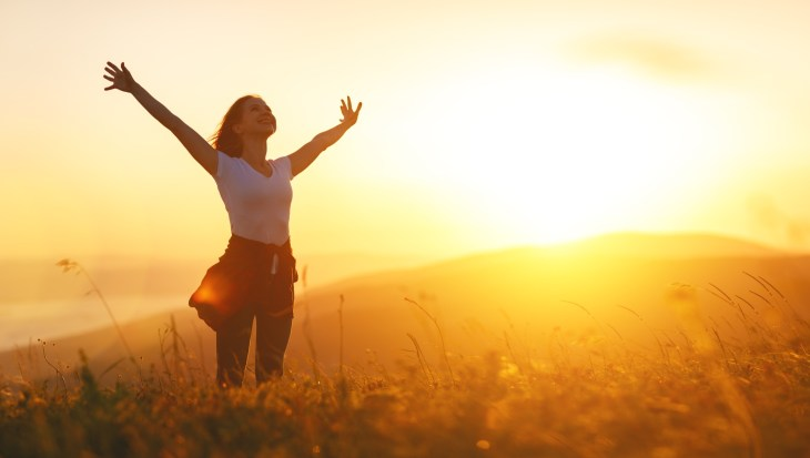 A woman in a field with the sun shining