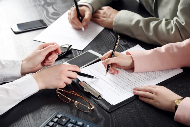 Three people filling out paperwork and going over documents