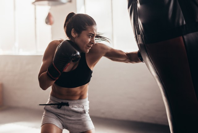 girl in black sports bra and gray shorts boxing in a ring