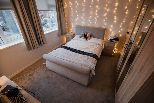 Empy student bedroom decorated with twinkle lights and teddy bears.