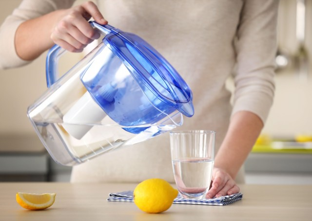 Woman pouring water from filter jug into glass in the kitchen