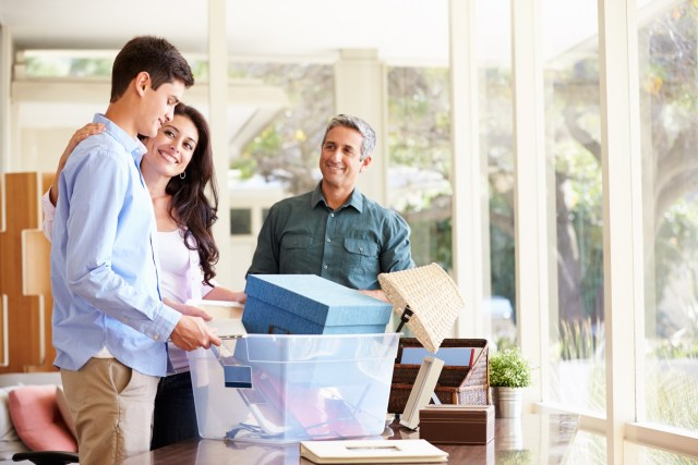 Parents Talking To Child And Helping Teenage Son Pack For College