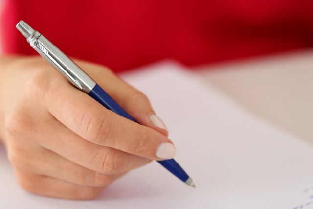 Female hand holding silver pen closeup. Woman writing letter, self development and perfection concept