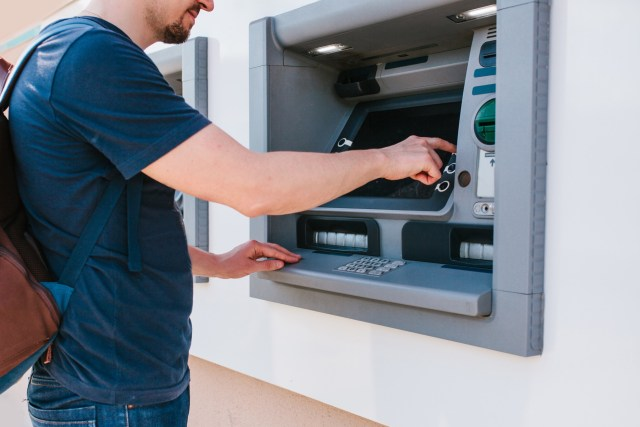 Man withdraws money from the ATM. Finance, credit card, withdrawal of money.