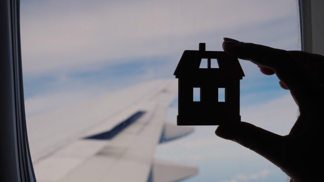 Silhoutte of a woman's hands holding a house.