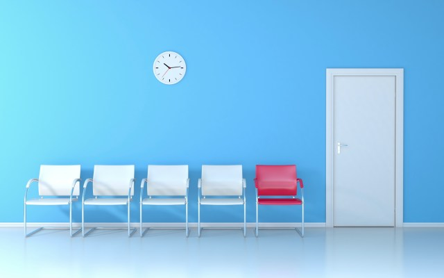 Blue waiting room with four white chairs and one red chair.