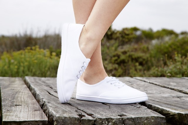 A girl showing off her white sneakers.