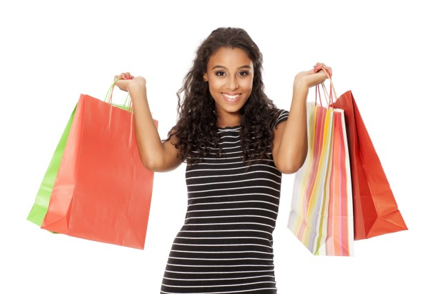 Young black girl holding shopping bags looking happy