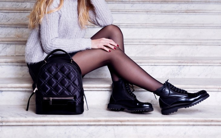 Girl wearing black Doc Martens and a matching bag