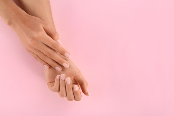 Manicured hands in front of a pink background