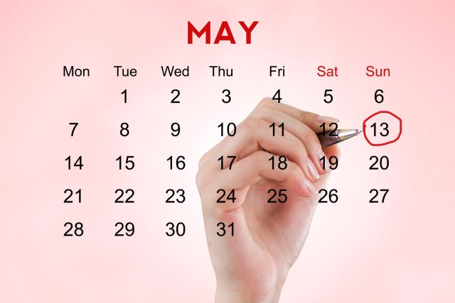 A woman, circling the 13th of May on her calendar.