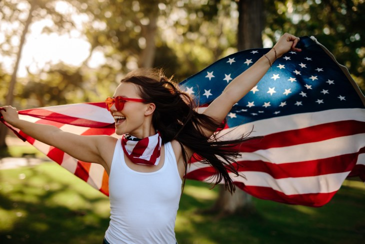 Woman holding American flag behind her back