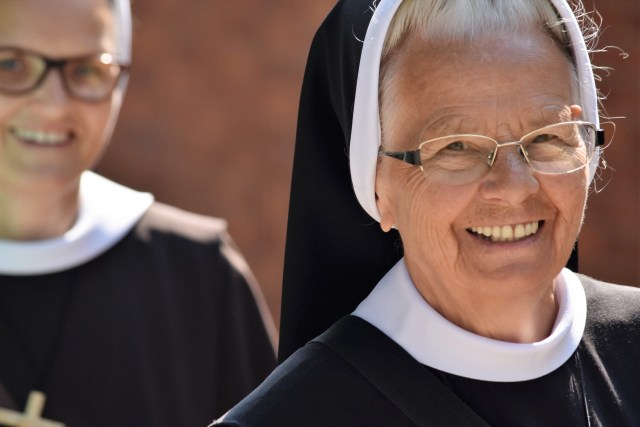 An elderly nun, smiling.