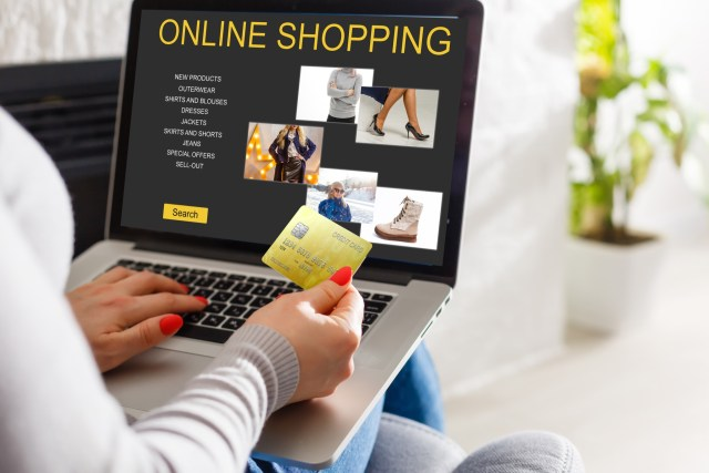 A young woman preparing to shop online, holding her gold credit card