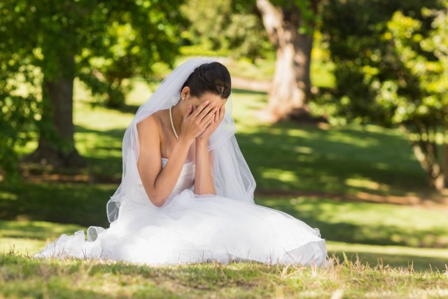 An unhappy, brunette bride, sitting in a park.