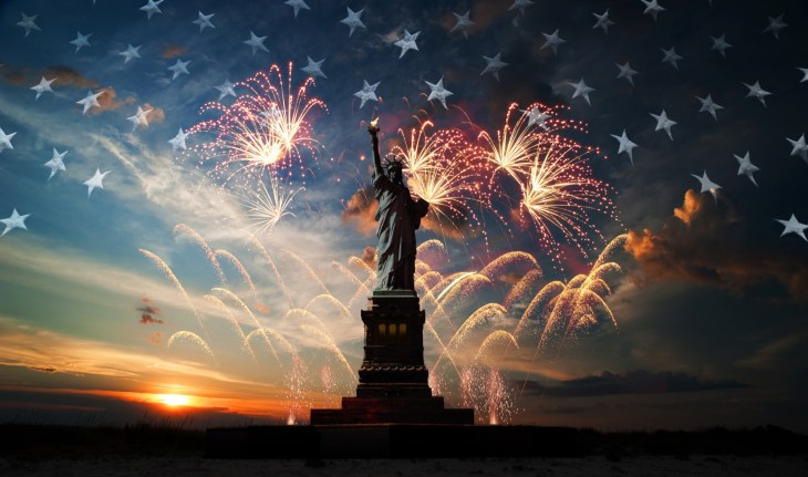 Statue of Liberty displayed by a sunset sky with fireworks