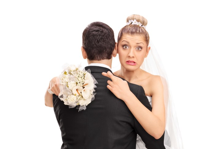 Confused bride, hugging her husband tightly while crossing fingers for good luck on isolated white background.