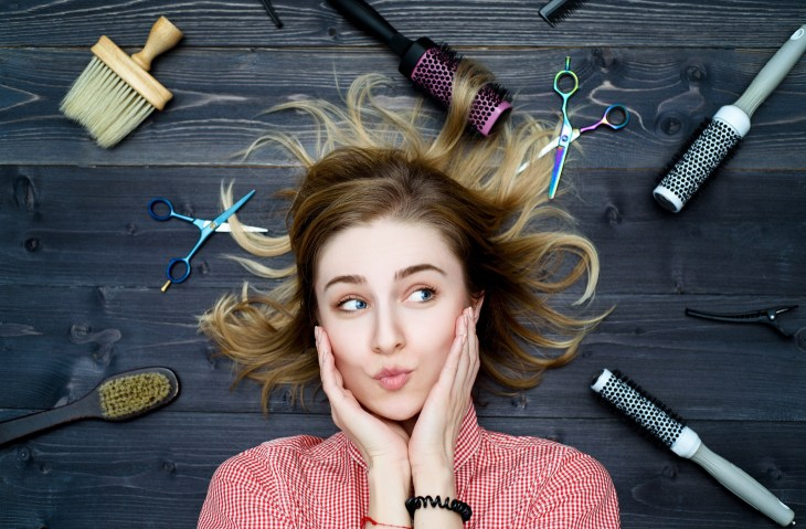 Woman surrounded by hairdresser tools