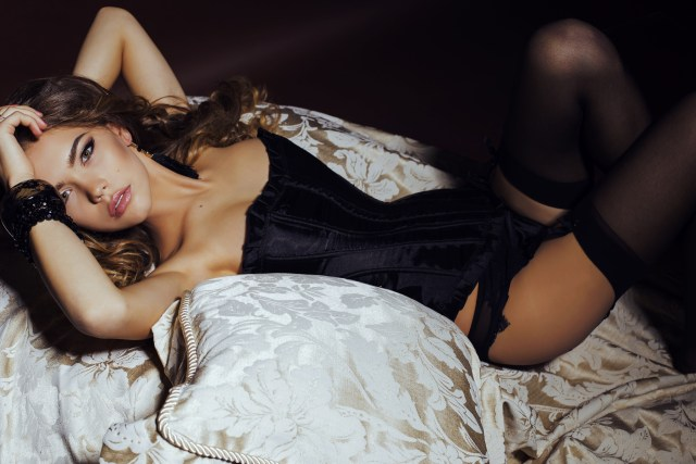 Woman on a bed wearing a black corset lingerie set