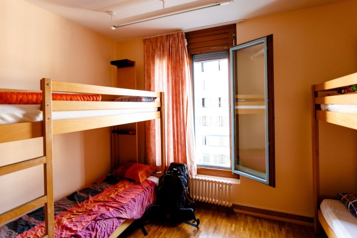College dorm room with wooden furniture and pink bedding