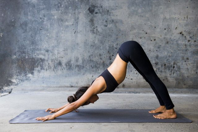 Woman practicing the downward facing dog yoga pose on her yoga mat