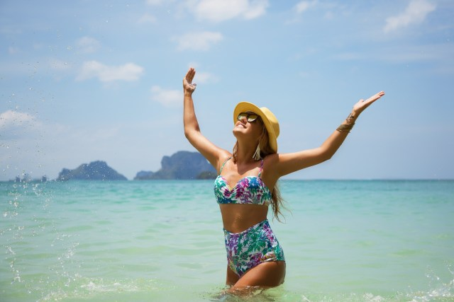 Woman splashing in the ocean wearing a high waisted swim suit