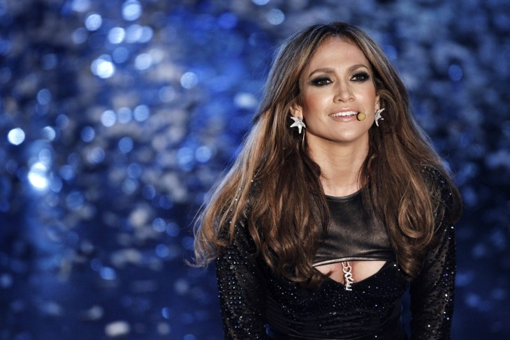 jennifer lopez staring out in front of blue background wearing black dress