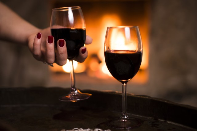Woman hand holds the wine glass in front of the fireplace.