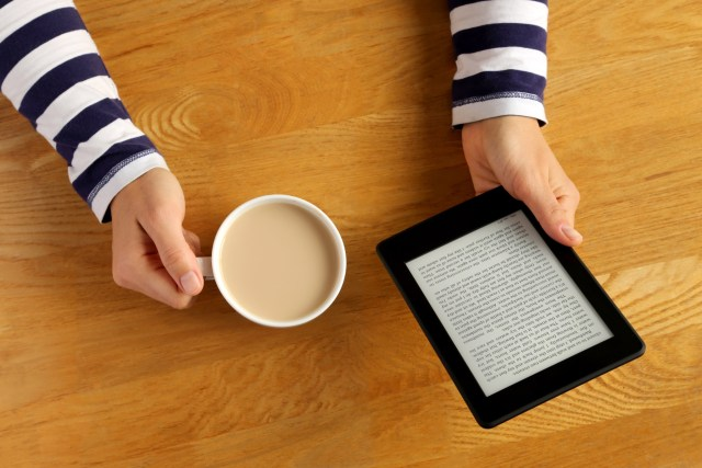 Hand holding Kindle, cup of coffee
