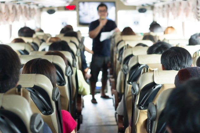 Passengers on a tour bus listening attentively to a guide