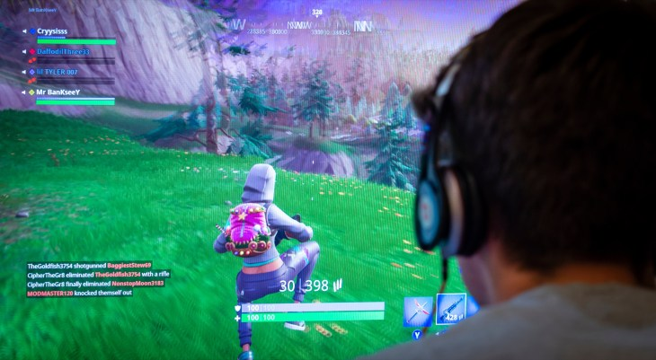 Teenager playing Fortnite video game, Fortnite is a web based multi player survival game developed by Epic Games