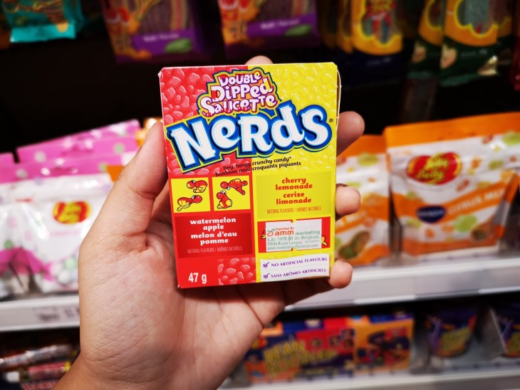 Hand hold a packet of NERDS Double Dipped Saucette candy in the supermarket