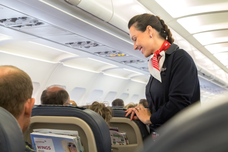 A female flight attendant is speaking with a passenger sitting in the economy class of the route Thessaloniki - Múnich of Eurowings Airline