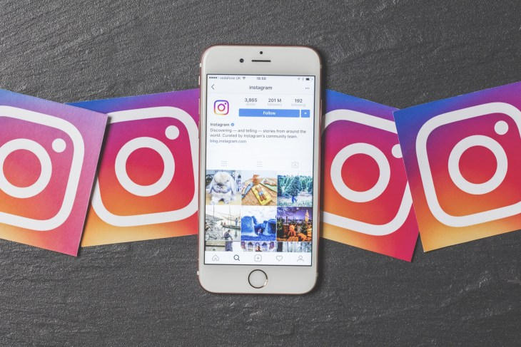OXFORD, UK - DECEMBER 5th 2016: An apple iPhone showing the instagram application alongside other instagram printed logos. Instagram is a popular social media application for sharing images and videos - Image