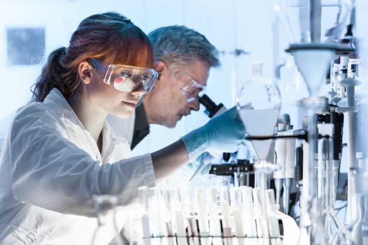 Health care researchers working in life science laboratory. Young female research scientist and senior male supervisor preparing and analyzing microscope slides in research lab. - Image