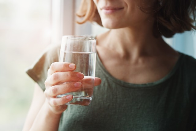 A woman holding a glass of water