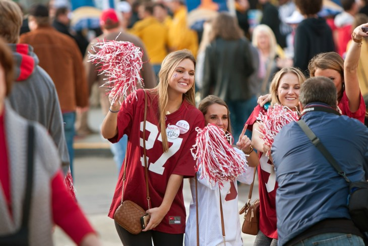 Female University of Alabama fans dressed in crimson pose for a photo as they walk to the Georgia Dome to watch the SEC Championship game