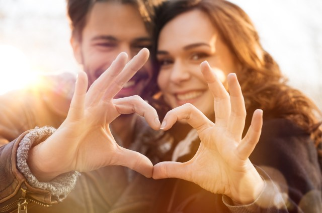 Closeup of couple making heart shape with hands.