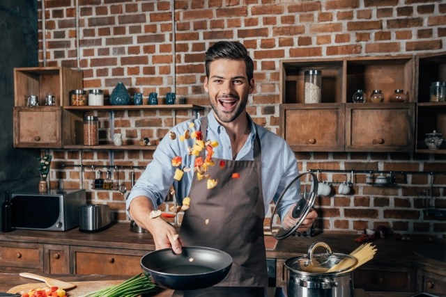 Handsome young man with apron frying vegetables for pasta
