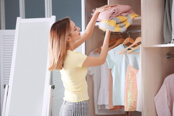 Young woman choosing clothes in wardrobe