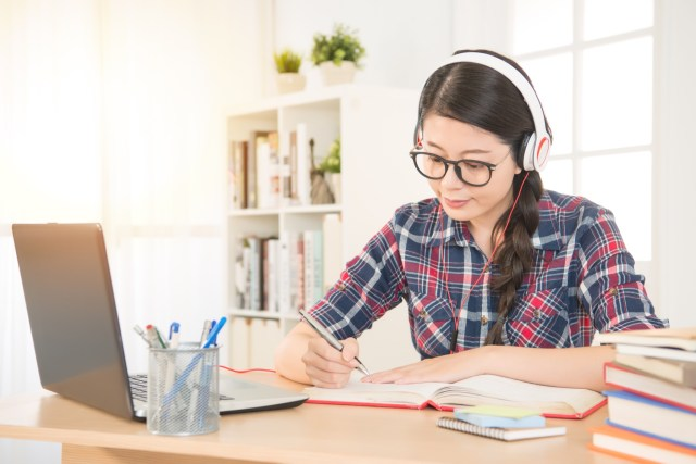 Portrait of a student learning on line with headphones and laptop