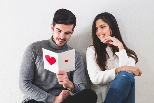 Happy couple with postcard