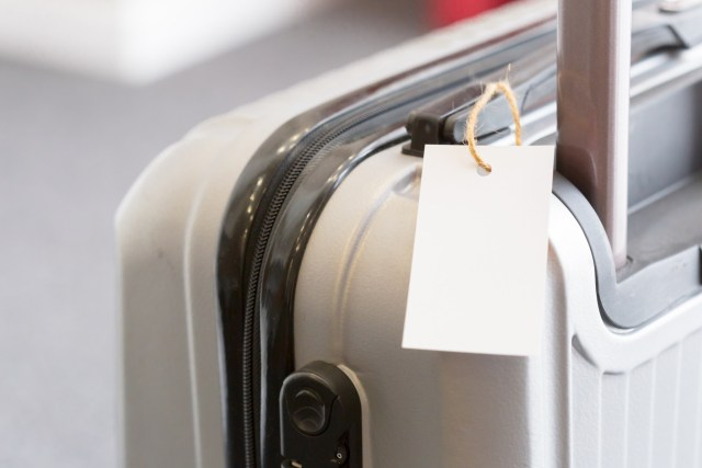 Close up of blank luggage tag label on a suitcase.